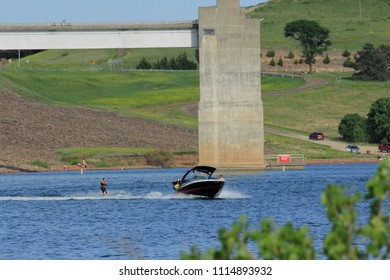 A shot of a Boat driving on Wilson Lake on the blue water. South of Lucas Kansas USA on 5-26-2018 with grass and tree's.
