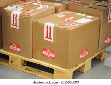 Shot of boxes on a wooden skid. The boxes are heavily marked up with fragile and handling stickers. Fragile Shipping