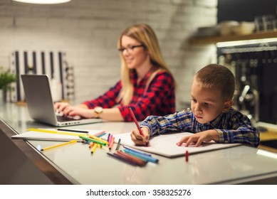 Shot of a boy drawing while his mother is working on a computer.