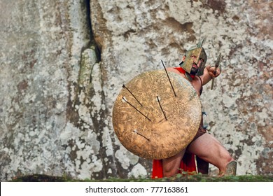 Shot of a brave Spartan protecting himself with a shield holding a spear fighting his archer enemy copyspace defence protection protective savior guardian fighter courage masculinity stance attack.