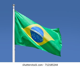 Shot of the Brazilian flag blowing in the wind with sky background