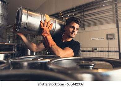 Shot of brewer carrying keg at brewery factory. Young man with metal beer barrels at warehouse.