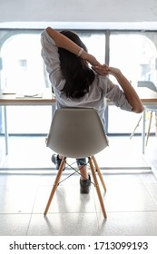 Shot of business woman taking a moment for relax and stretching in the office. Back view.