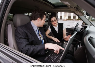 A shot of a businessman and businesswoman sitting in a car looking at a laptop.