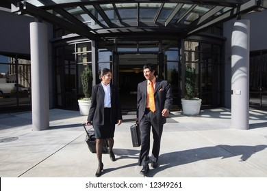 A shot of businessman and businesswoman walking out of building on sunny day.
