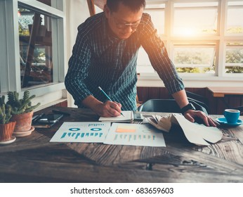Shot of businessman in casual clothes at modern startup business office space, working on wood table