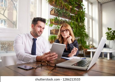 Shot of businessman holding digital tablet in his hand while his collegaue sitting next to him and working together on business plan. Teamwork in the office.