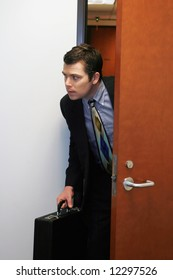 A shot of businessman peaking his head out of a door to see if he can sneak out the office.