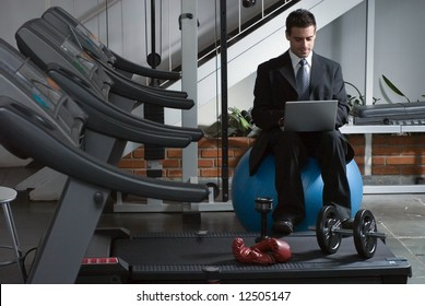 A shot of a businessman, in suit, checking email by row of treadmills.