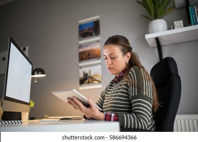 Shot of a busy woman working from home using digital tablet.