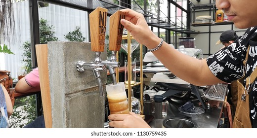 A shot of a cafe worker pouring a Nitro Cold Brew Coffee from the tap to a cold glass before serving to customer in Bangkok, Thailand on 8th July 2018