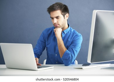 Shot of a careworn young man sitting in front of laptop and working online.