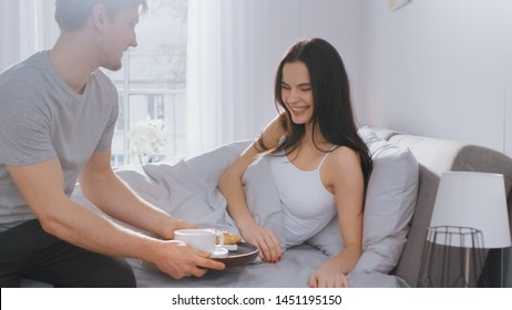 Shot of a Caring Young Man Bringing Tray with Breakfast in Bed to His Lovely Female Partner. Ideal Tender Relationship and Coffee and Croissants in Bed.
