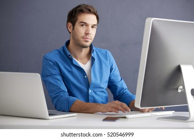 Shot of a casual young businessman sitting at office in front of computer and working online.