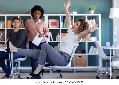 Foto de una joven empresaria casual divirtiéndose en la oficina mientras sus colegas la miran.