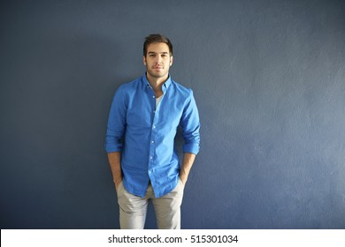Shot of a casual young man standing in front of a grey wall while looking at camera and smiling.