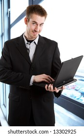 A shot of a caucasian businessman carrying a laptop in the office