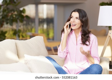 Shot of a charming young woman enjoying a conversation on her mobile phone while sitting on sofa at home.