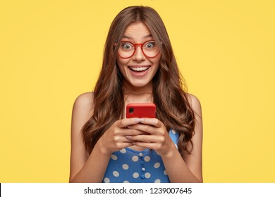 Shot of cheerful female model wears glasses, holds cell phone, takes pictures, talks via video message, has nice friendly talk, dressed in fashionable outfit, isolated over yellow background