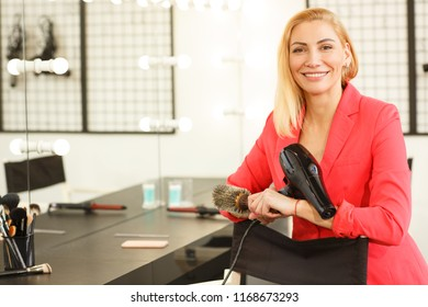 Shot of a cheerful female professional hairstylist smiling to the camera posing proudly at her workplace holding blow dryer copy space. Profession, stylist, beauty industry concept
