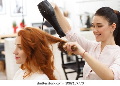 Shot of a cheerful hairdresser blow drying hair of a beautiful young woman, working at her beauty salon. Attractive young ginger haired female gitting her hair dried by a professional stylist