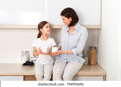 Shot of cheerful mother and daughter sit together at kitchen table, drink hot tea in morning, have pleasant friendly talk between each other. Curious girl asks something in mum during coffee break.