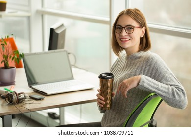 Shot of a cheerful young attractive businesswoman wearing glasses smiling happily to the camera holding thermos with her morning coffee sitting at the office in front of her laptop copyspace.