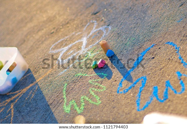 A shot of a child write on the street by using chalk color