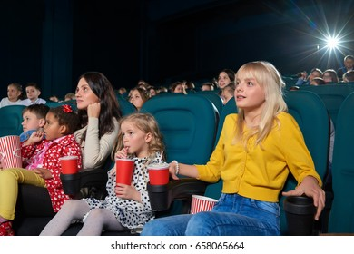 Shot of children watching a movie at the cinema. Movie theatre auditorium full of kids entertaining hobby leisure activity people lifestyle emotions fun conept.