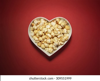 Shot of cinema style popcorn in a heart shaped bowl on a vibrant and bright red background with copy space and a clipping path.