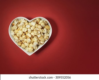 shot of cinema style popcorn in a heart shaped bowl on a bright red background with spotlit, vignette style lighting and offset with plenty of copy space for the designer.
