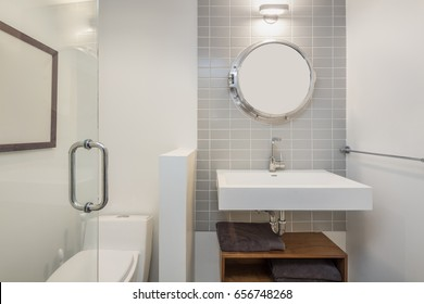 Shot of clean modern bathroom with tiled wall and round mirror