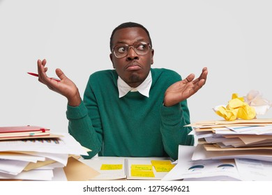 Shot of clueless dark skinned man shruggs shoulders with hesitation, cant decide which investor to choose, does paper work in coworking space, dressed casually, isolated over white background