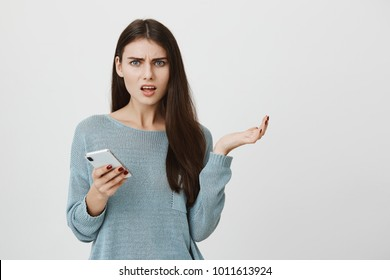 Shot of clueless young caucasian brunette woman looking at camera with confused and puzzled expression, frowning, being displeased with received message, holding in her hands modern smartphone