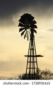 A shot of a colorful Kansas Sunset with clouds and a Windmill silhouette north of Hutchinson Kansas USA out in the country.