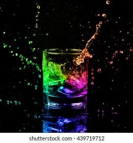 shot of colorful whiskey with splash on black background