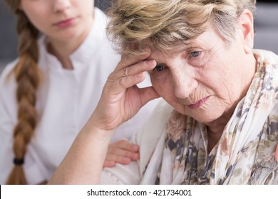 Shot of a concerned senior woman and a nurse sitting behind her and holding her arm
