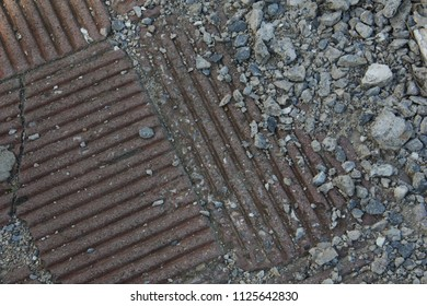 A shot of concrete rubbles on the red stripes tiles floor. Background / Textures