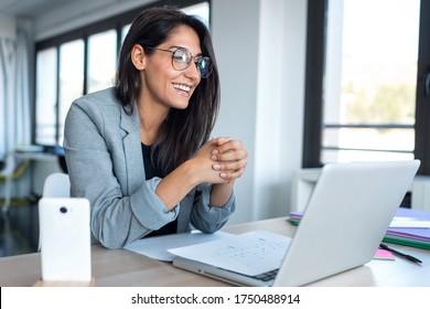 オフィスでノートパソコンを使ってビデオ会議を行う際に、ウェブカメラを通して見たり話したりする自信のあるビジネスマンの写真。