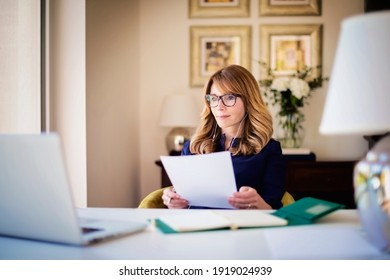 Shot of confident woman sitting behind her laptop and having video call while working from home. Home office.