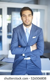 Shot of a confident young businessman looking at camera and smiling while standing at desk after business meeting.