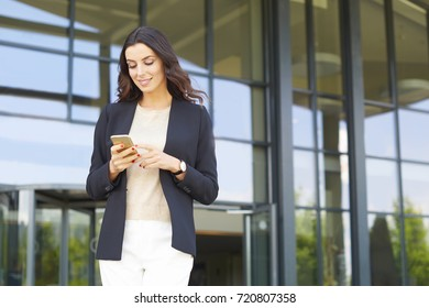 Shot of a confident young businesswoman text messaging while standing in front of office building and waiting for taxi driver.