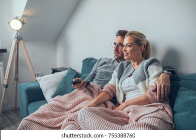 Shot of a couple resting on the couch watching television
