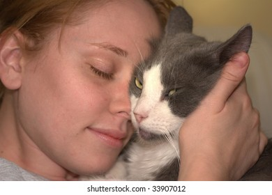 Shot of a cute girl and cat holding each other face to face