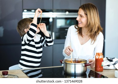 Shot of cute little boy having fun with his young mother while eating spaghetti on kitchen at home.