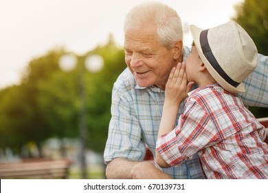 Shot of a cute little boy whispering something to his grandfather while resting together outdoors copyspace family communication relationships trust happiness love gossip children kids parenting