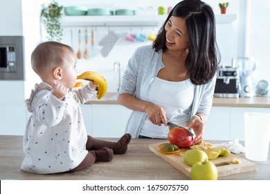 Shot of cute little girl playing with food while her mother cuts fruit to prepare baby porridge in the kitchen.