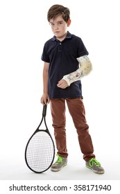 Shot of a cute young boy who has broken his left arm and is unhappy because he can't play tennis
