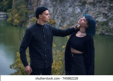 Shot of a dangerous laughing man choking blue hair girl