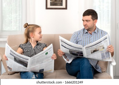 Shot of a daughter and dad spending time together at home. They sit on the sofa and read the newspapers together same way.  Daughter imitates her father.